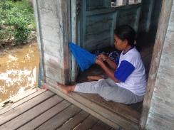 Fisherwoman in Taruna Jaya making a fishing net. Photo by Sara Thornton.