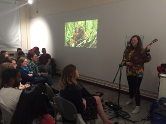 Jenny Hibberd performing with the peat swamp video in the background, Into the Swamp
